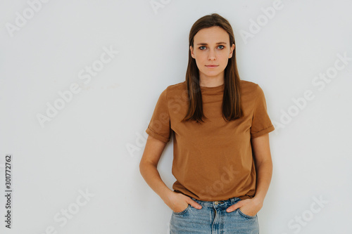 Fotografija Portrait of a woman, leaning on the wall, with hands in pockets