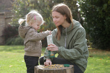 Mother And Her Toddler Girl Putting Seeds For Birds In A Bird Feeder. Quality Outdoor Family Time Together. Encouraging Wildlife In The Garden With Bird Feeder.
