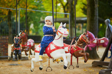 Toddler Having Fun On Vintage French Merry-go-round In Paris