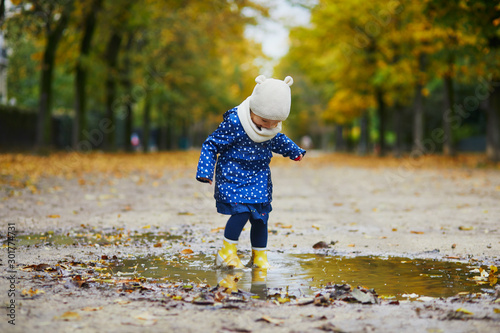 Stampa su Tela Child wearing yellow rain boots and jumping in puddle