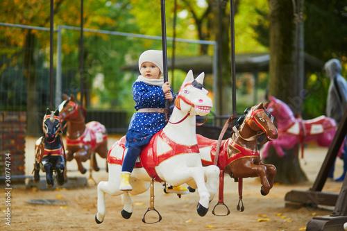Vászonkép Toddler having fun on vintage French merry-go-round in Paris
