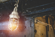 Close Up Of Old Vintage Lamp Or Light Bulb On Ship Deck Wall Surrounded By Metal Rustic. Bulkhead Light On Navy Ship With Rust And Dust.