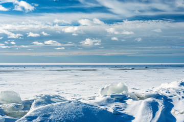 winter landscape of the Gulf of Finland with cloudy sky and ice floes under the snow
