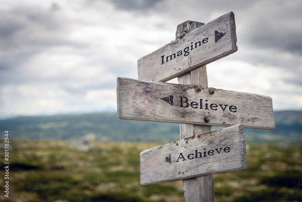 Fototapeta Imagine, believe and achieve text on wooden sign post outdoors in landscape scenery. Business, quotes and motivational theme concept.