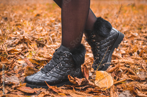 Fotomural  A girl in beautiful warm boots stands in autumn orange leaves, a photo for fashi