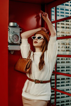 Outdoor Autumn Fashion Portrait Of Young Elegant Woman Wearing Stylish Brown Leather Beret, Sunglasses, White Sweater, Belt, Holding Classic Purse, Handbag, Posing In Red Call Box