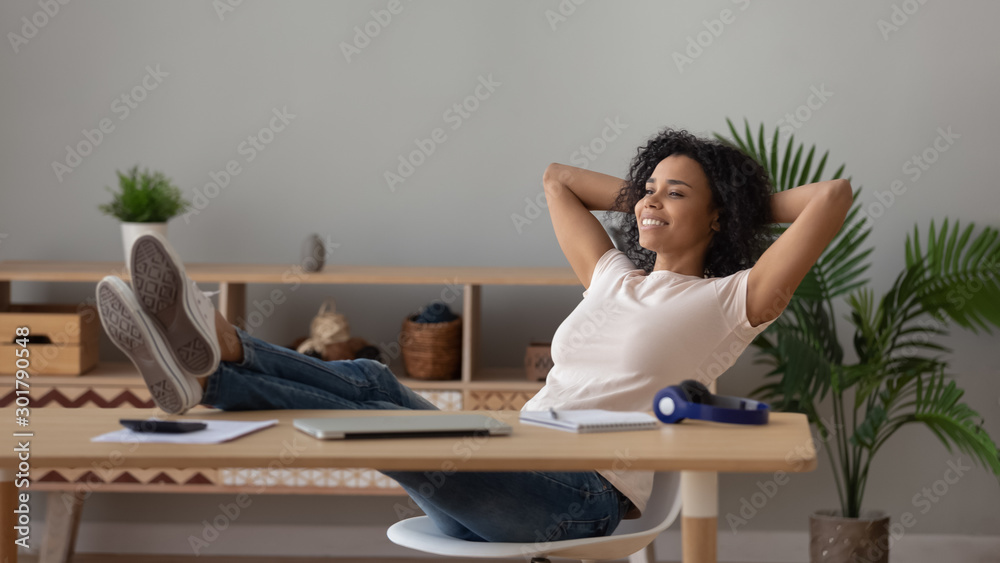 Fototapeta Satisfied African American woman relaxing with legs on table
