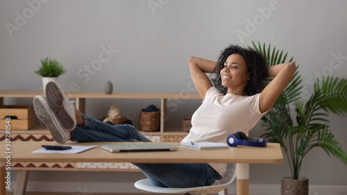 Fotografía  Satisfied African American woman relaxing with legs on table