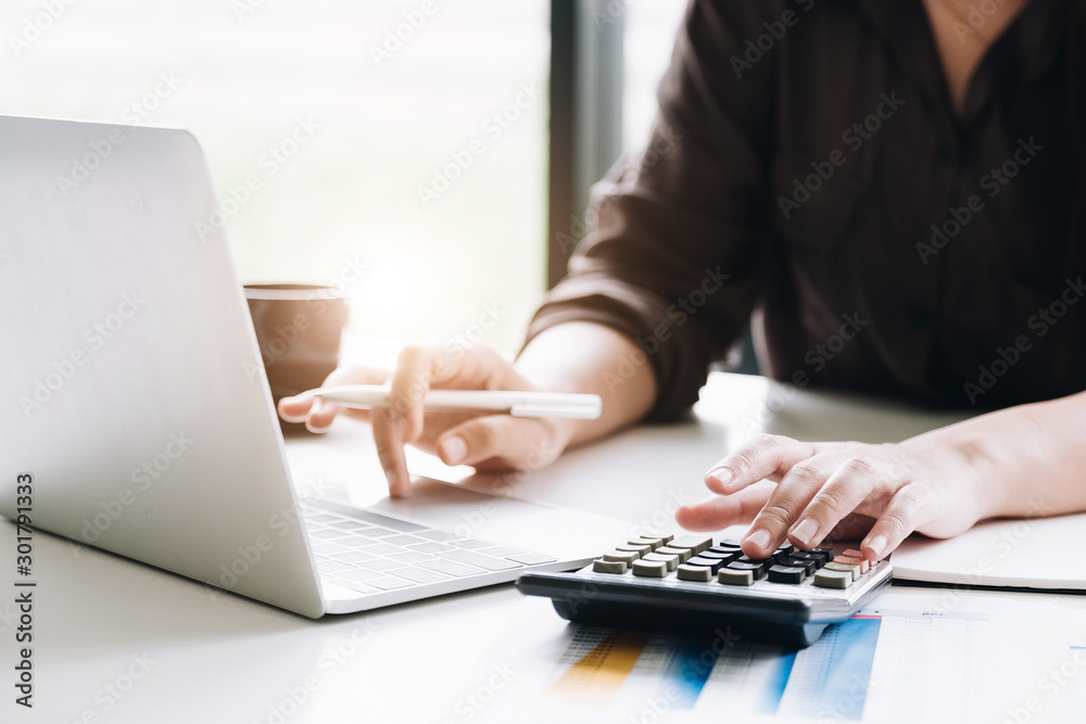 Fototapeta Close up of busineswosman or accountant hand holding pen working on calculator to calculate business data, accountancy document and laptop computer at office, business concept