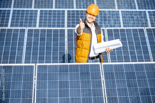 Fotografija Portrait of a handsome engineer in protective helmet standing with blueprints on a solar power plant