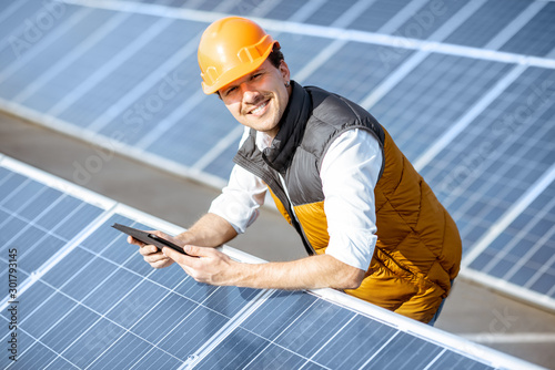 Slika na platnu Portrait of a happy engineer in protective helmet standing with digital tablet on a solar power plant