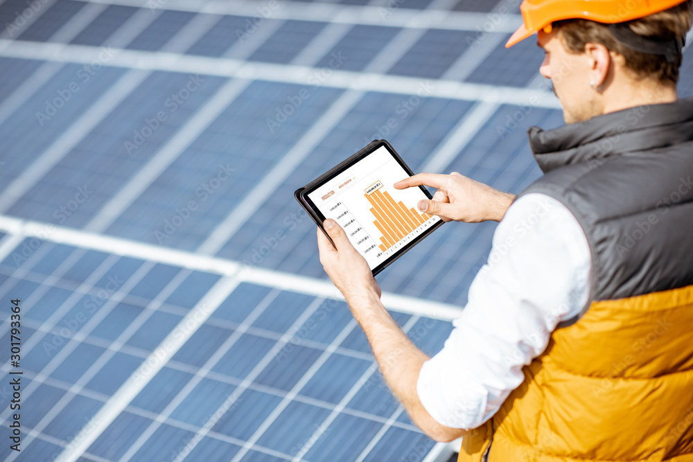Fototapeta Man examining genaration of solar power plant, holding digital tablet with a chart of electricity production. Concept of online monitoring of the electric station