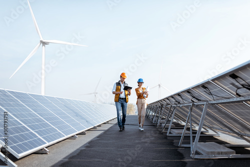 Obraz View on the rooftop solar power plant with two engineers walking and examining photovoltaic panels. Concept of alternative energy and its service - fototapety do salonu