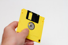 Yellow Floppy Disk In Hand. Ma...