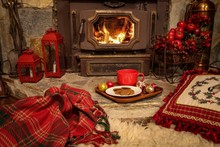 Christmas Decorations On A Rustic Stone Fireplace With Red Mug On Wooden Platter With Cookies Ready For Santa Claus, With A Pretty Black Cat Sleeping Cozily