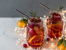 Winter Sangria In Mason Jars With Metal Straws On Christmas Holiday Background. Decorated Fruit Slice, Cranberry And Rosemary. Copy Space For Text Or Design. Horizontal. Decoration Lighting Chain