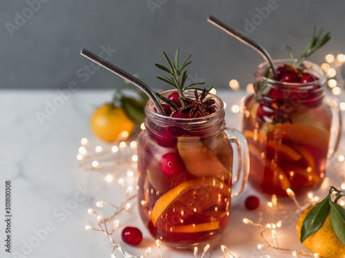 Recess Fitting Alcohol Winter sangria in mason jars with metal straws on christmas holiday background. Decorated fruit slice, cranberry and rosemary. Copy space for text or design. Horizontal. Decoration lighting chain