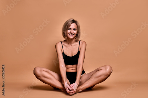 Obraz Girl with vitiligo disease covers her face with hands, closeup portrait on beige background - fototapety do salonu