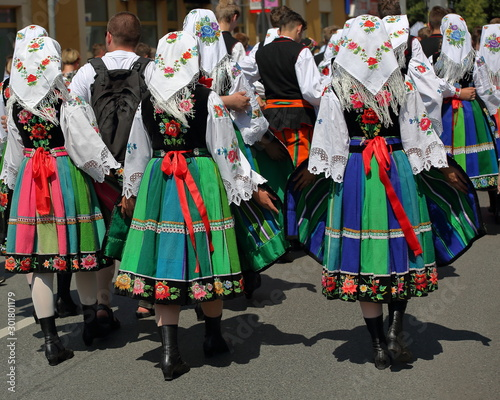 Foto Local Polish people in traditional folk costumes from Lowicz region walk on stre