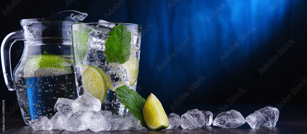 Fototapeta Glass of mineral water with ice, lime and mint
