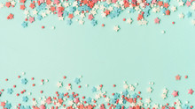 Festive Border Frame Of Colorful Pastel Sprinkles On Blue Background With Copy Space In Center. Sugar Sprinkle Dots And Stars, Decoration For Cake And Bakery. Top View Or Flat Lay. Banner