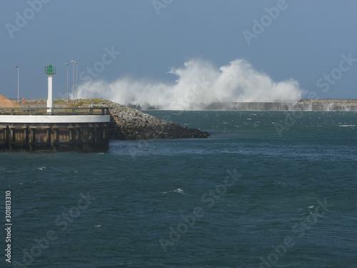 Fotomural tempête vague qui s'écrase sur une digue