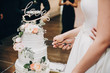 canvas print picture - Bride and groom cutting stylish wedding cake at wedding reception in restaurant. Wedding couple holding knife and cutting together wedding cake decorated with flowers