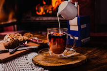 Pouring Milk From Porcelain Milk Jug Into Cup Filled With Tea - White Tablecloth And Fire Background. Winter Mood
