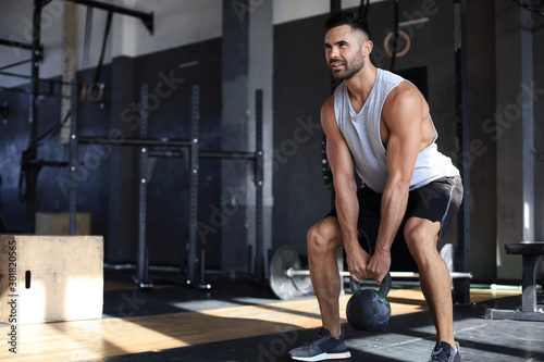 Fit and muscular man focused on lifting a dumbbell during an exercise class in a gym Fototapeta