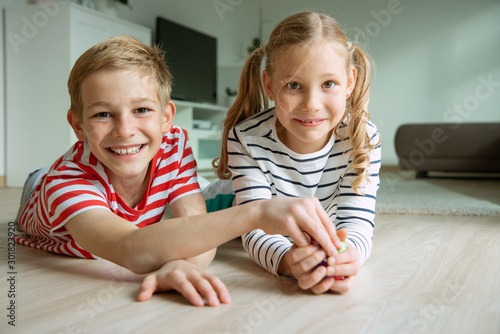 Photo  Portrait of two cheerful children laying on the floor and playing with colorful