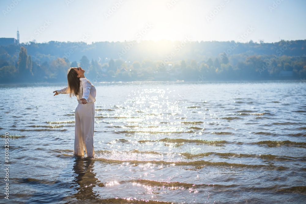 Fototapeta Woman in white opening her arms to the sun in the water