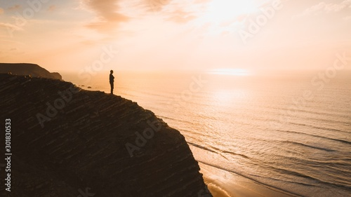 Obraz Beautiful view of a person standing on a cliff over the ocean at sunset in Algarve, Portugal - fototapety do salonu