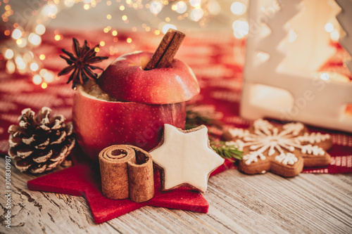 Fototapeta christmas baked apple for christmas in christmas decoration with cinnamon stick and orange and advent candle obraz