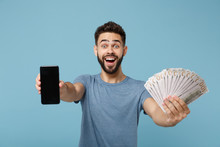Young Surprised Man In Casual Clothes Posing Isolated On Blue Background. People Lifestyle Concept. Mock Up Copy Space. Hold Mobile Phone With Blank Empty Screen Fan Of Cash Money In Dollar Banknotes.