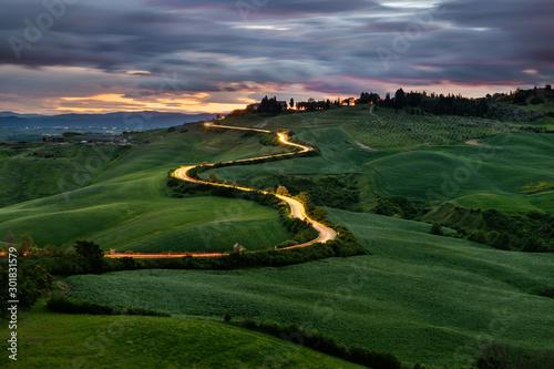 Kręta droga, światła samochodów, zachód słońca w tle, Toskania, Włochy - 301831579