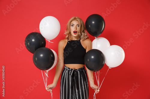 Photo  Shocked young woman girl in black clothes posing isolated on red background