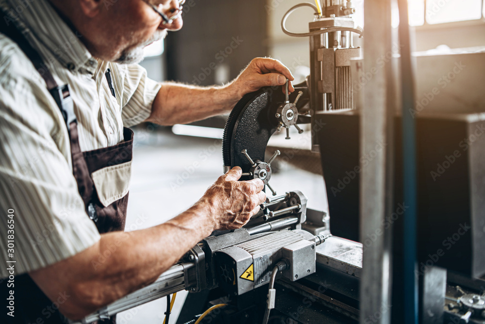 Fototapety, obrazy: Adult proffesional worker on the factory working with machinery.