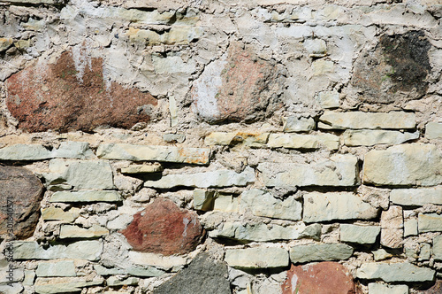 Fragment of wall made of rough uneven stones of different types: granite, flagstone, limestone #301840571