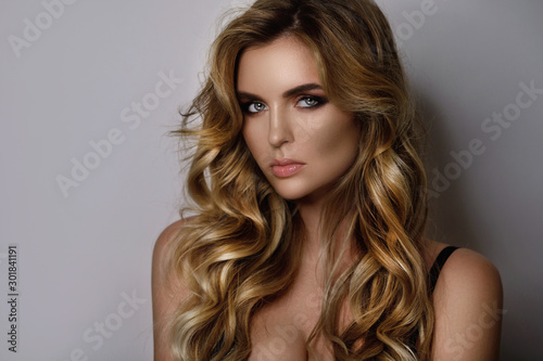 Fototapeta  Gorgeous woman with a beautiful curly hair and professional makeup