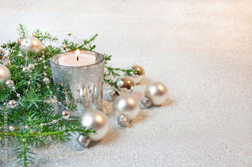 Obraz Srebrne bożonarodzeniowe tło ze świecą, bombkami i gałązkami jałowca - fototapety do salonu