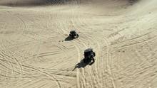 Off Road Bike & ATV Quad Vehicles Driving Sandy Imperial Dunes Leaving Tracks. Aerial Tilt Up View.