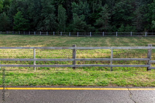 artiodactyla pasture fenced by a wooden fence on the side of the road near an asphalt road with yellow markings, no animals Canvas Print
