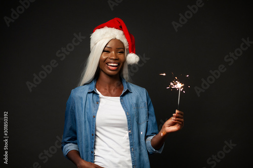 Fotografía  African Girl in Christmas Hat Holds Bengal Fire