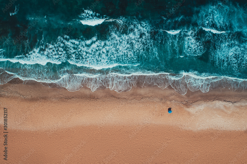 Fototapeta Aerial top view from drone of sandy beach with turquoise sea waves with copy space for text