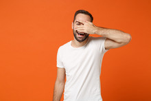 Cheerful Young Man In Casual White T-shirt Posing Isolated On Orange Wall Background, Studio Portrait. People Sincere Emotions Lifestyle Concept. Mock Up Copy Space. Hiding, Covering Eyes With Hand.