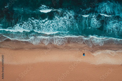 Fototapeta Aerial top view from drone of sandy beach with turquoise sea waves with copy space for text obraz