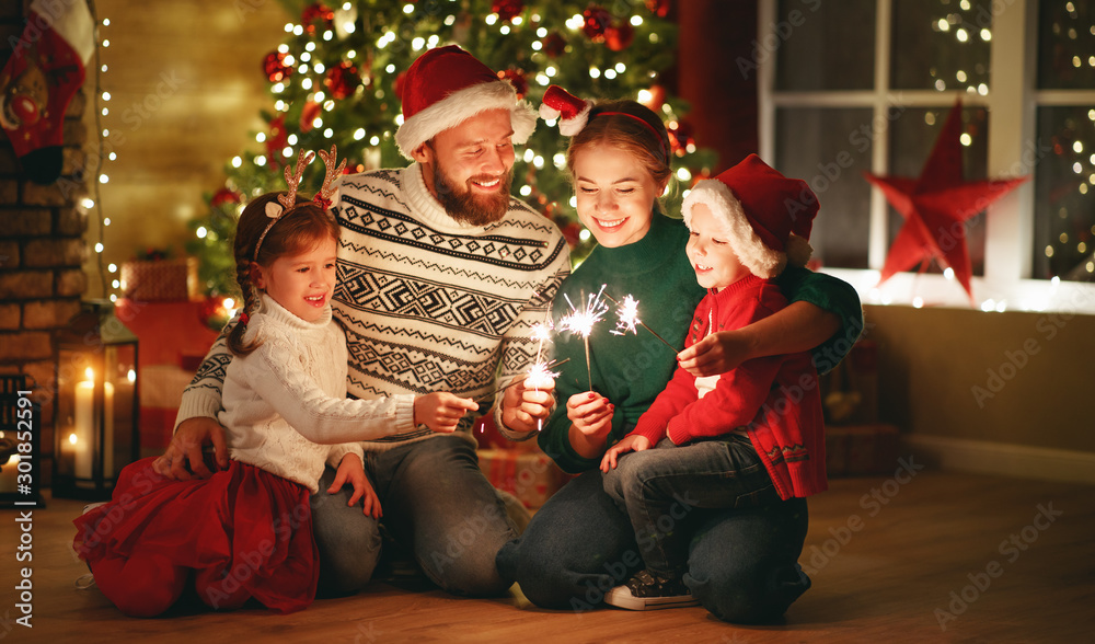 Fototapeta happy family mother, father and children celebrate Christmas and new year, light sparklers.