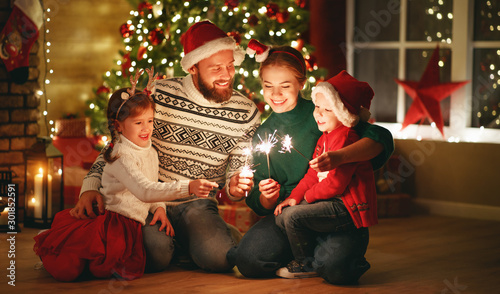 Fotomural  happy family mother, father and children celebrate Christmas and new year, light sparklers