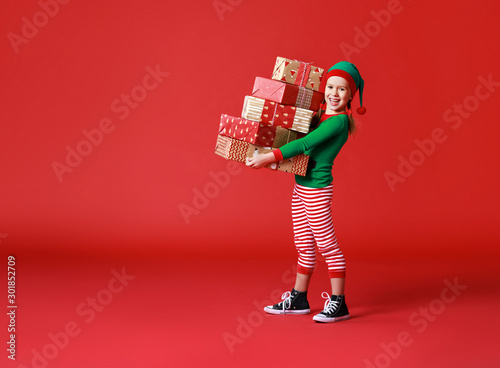 Pinturas sobre lienzo  cheerful funny child in Christmas elf costume with gifts on   red background