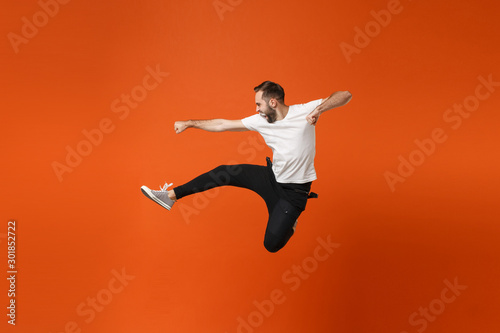 Photo Crazy young man in casual white t-shirt posing isolated on orange wall background studio portrait